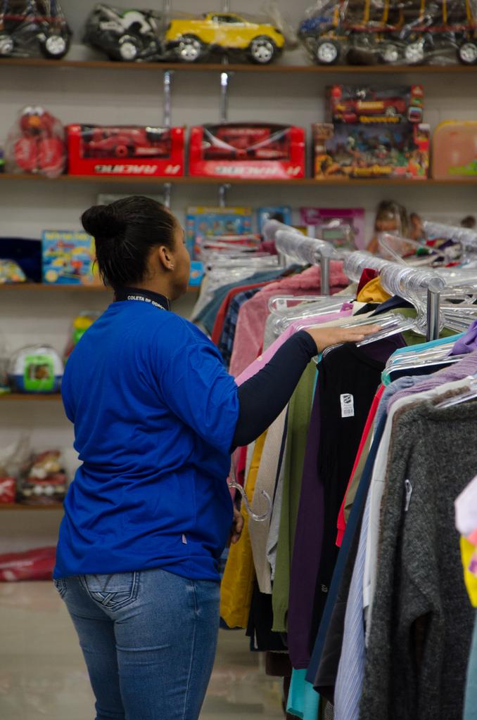 Funcionária dá os últimos retoques nas araras de roupas antes da abertura da loja.